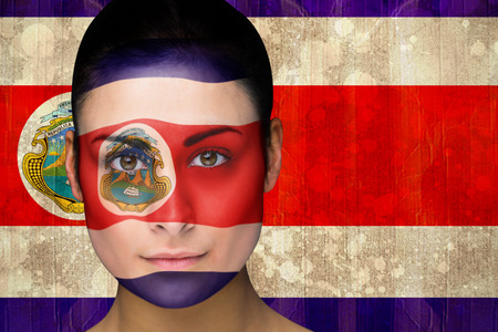 Composite image of beautiful football fan in face paint against costa rica flag in grunge effect photo