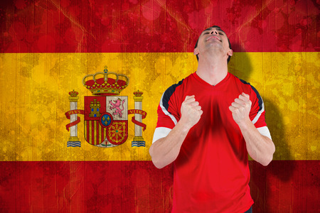 Excited football fan cheering against spain flag in grunge effect photo