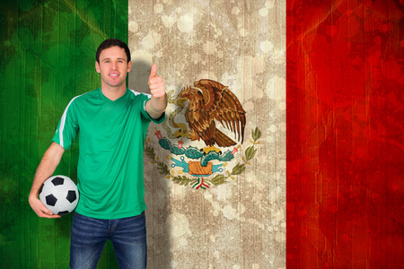 Handsome football fan in green against mexico flag in grunge effect photo