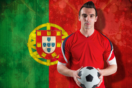 Handsome football fan looking at camera against portugal flag in grunge effect photo