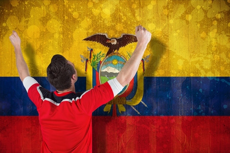 Excited football fan cheering against ecuador flag in grunge effect photo