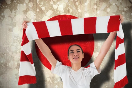 Composite image of football fan waving red and white scarf against japan flag photo