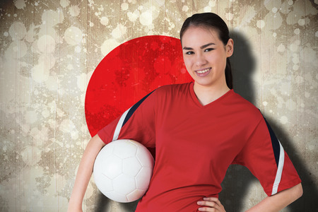 Composite image of smiling asian football fan looking at camera against japan flag photo