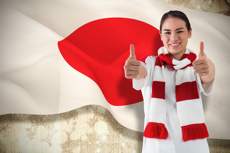 Composite image of football fan in white wearing scarf showing thumbs up against japan flag photo