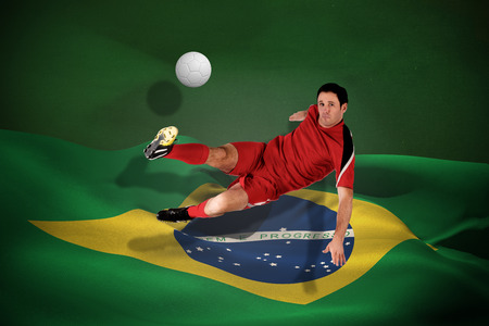 Football player in red kicking against white leather football with shadow photo