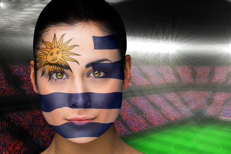 Composite image of beautiful uruguay fan in face paint against large football stadium with fans in blue photo