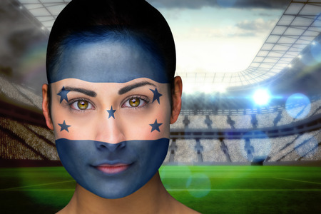 Composite image of beautiful honduras fan in face paint against vast football stadium with fans in white photo