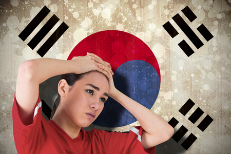 Disappointed football fan looking down against south korea flag photo