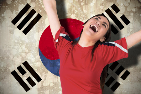 Composite image of excited asian football fan cheering against south korea flag photo