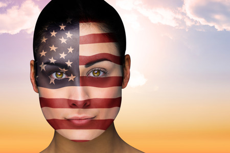 Composite image of beautiful brunette in america facepaint against beautiful orange and blue sky photo