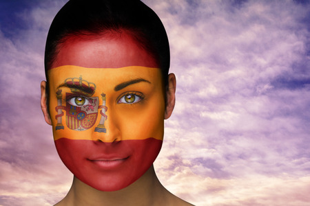 Composite image of beautiful brunette in spain facepaint against scenic landscape with blue cloudy sky photo