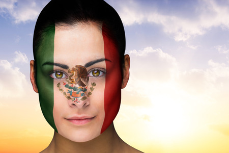 Composite image of beautiful brunette in mexico facepaint against beautiful orange and blue sky photo
