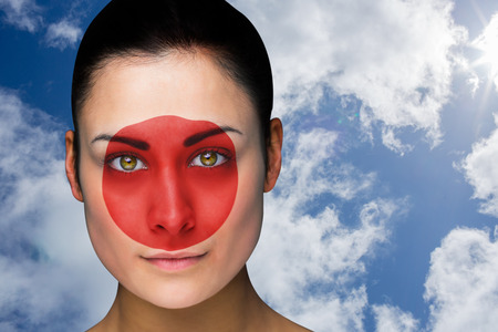 Composite image of beautiful brunette in japan facepaint against bright blue sky with clouds photo