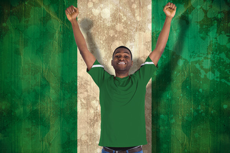 Cheering football fan in green jersey against nigeria flag in grunge effect photo