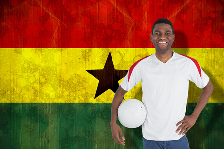 Handsome football fan looking at camera against ghana flag in grunge effect photo