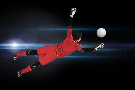 goal keeper: Fit goal keeper jumping up against black background with spark