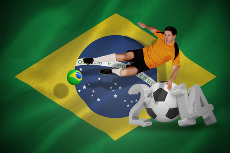 Football player in orange jumping against world cup 2014 with brasil flag photo
