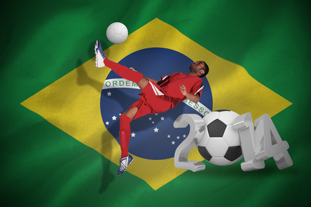 Football player in red kicking against world cup 2014 with brasil flag photo
