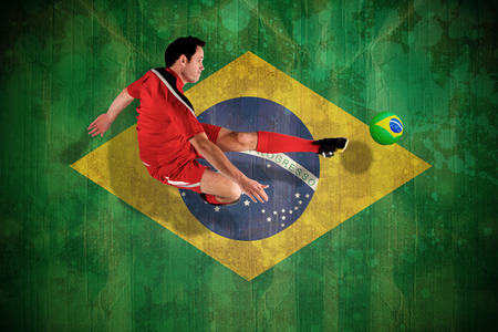 Football player in red kicking against brazil flag in grunge effect photo