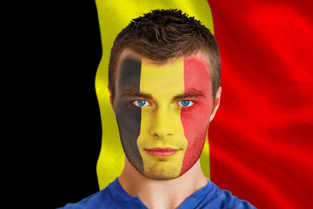 Composite image of serious young belgium fan with facepaint against belgium flag photo