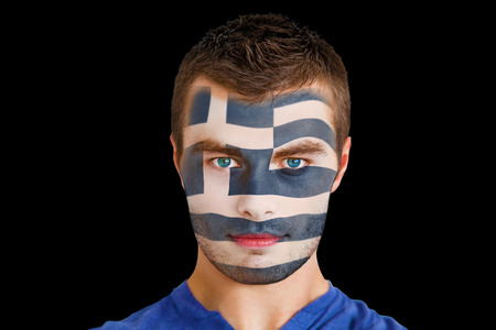 Composite image of serious young greece fan with facepaint against black photo