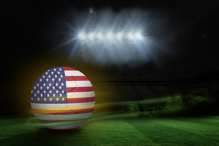 Football in america colours  against football pitch under spotlights photo