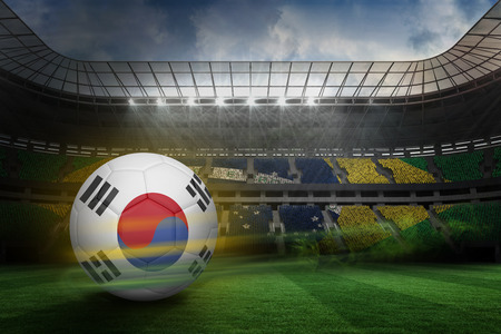 Football in south korea colours  against large football stadium with brasilian fans photo