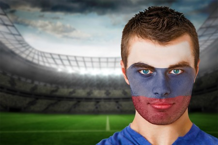 Composite image of russia football fan in face paint against large football stadium with lights photo