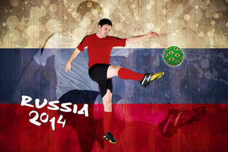 Football player in red kicking against russia flag in grunge effect photo