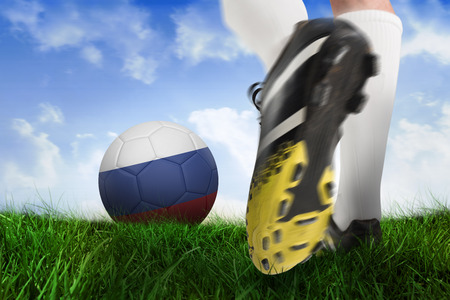 Composite image of football boot kicking russia ball against field of grass under blue sky photo
