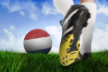Composite image of football boot kicking netherlands ball against field of grass under blue sky photo