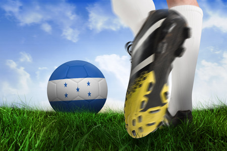 Composite image of football boot kicking honduras ball against field of grass under blue sky photo