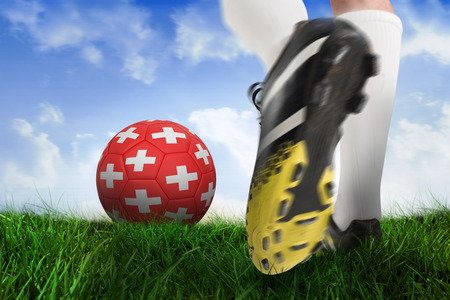 Composite image of football boot kicking switzerland ball against field of grass under blue sky photo