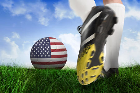 Composite image of football boot kicking usa ball against field of grass under blue sky photo