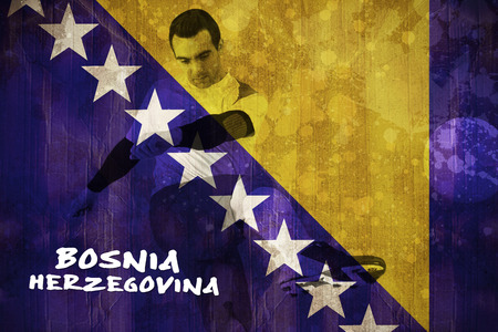 Football player in white kicking against bosnia flag in grunge effect photo