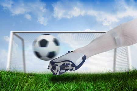 goalpost: Composite image of close up of football player kicking ball against goalpost on grass under blue sky