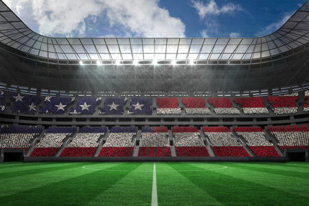 Digitally generated american national flag against large football stadium photo