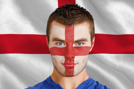 Composite image of serious young england fan with facepaint against digitally generated english national flag photo