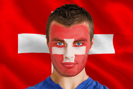 Composite image of serious young swiss fan with facepaint against digitally generated swiss national flag photo