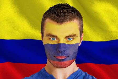 Composite image of serious young colombia fan with facepaint against digitally generated colombia national flag photo