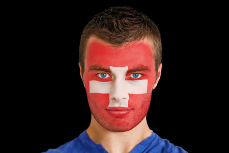 Composite image of serious young swiss fan with facepaint against black photo
