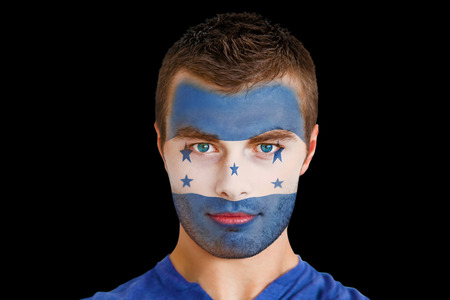 Composite image of serious young honduras fan with facepaint against black photo