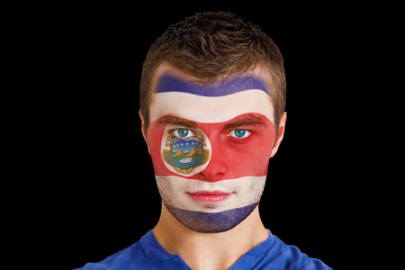 Composite image of serious young costa rica fan with facepaint against black photo
