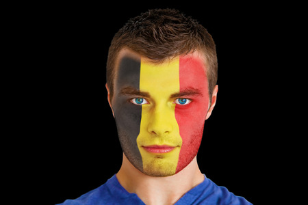 Composite image of serious young beligan fan with facepaint against black photo