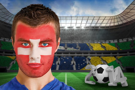 Composite image of serious young switzerland fan with facepaint against large football stadium photo
