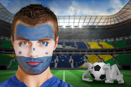 Composite image of serious young honduras fan with face paint against large football stadium  photo