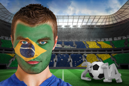 Composite image of serious young brasil fan with face paint against large football stadium with brasilian fans photo