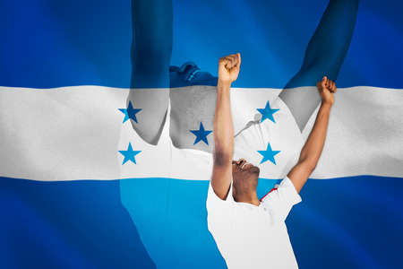 Excited handsome football fan cheering against digitally generated honduras national flag photo