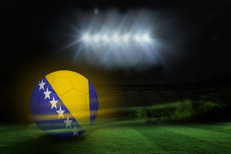 Football in bosnia and herzegovina colours against football pitch under spotlights photo