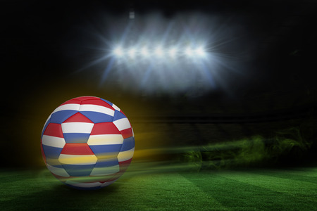 Football in holland colours  against football pitch under spotlights photo